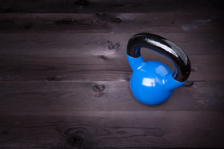 Sport equipment. Blue kettle bell on a black wooden background