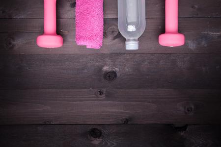 Équipement de sport. Bouteille d'eau, serviette rose et un haltère rose sur un fond en bois noir