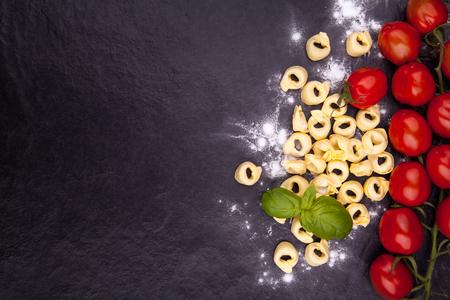 Tortellini, tomato, basil and flour on a black stone plate.