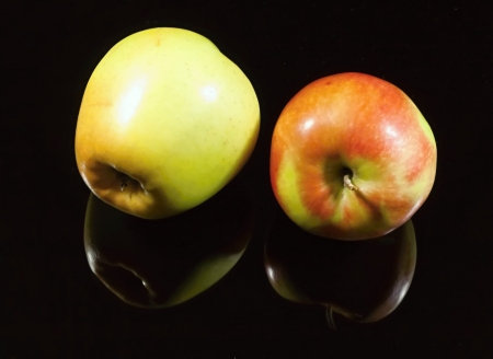 Two apples on black background with shadow