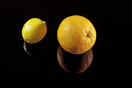 Orange and lemon on the black desk with shadows Stock Photo