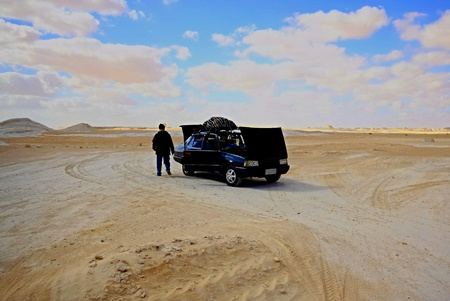 Lonely man in White desert with the car out of order Stock Photo