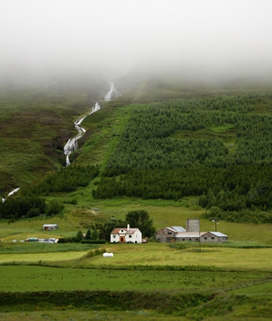 Farm houses and waterfall on backgroud,Iceland