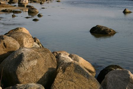 Large rocks warming in the sun by the water. Imagens