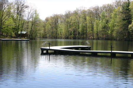 A lake with a dock surrounded by trees.