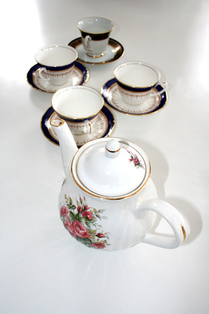 Fine China teapot and teacups on saucers sitting on a white table.