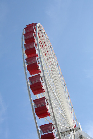 A Ferris wheel with glassed in red carriages isolated in the sky. Imagens