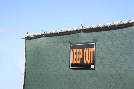 A green privacy fence with a KEEP OUT sign posted.