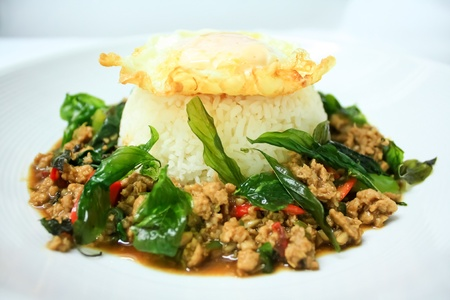 chicken sauteed with garlic and hot basil set on steamed rice with fried egg Stock Photo