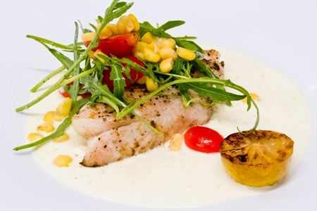white fish steak in cream sauce with rocket and corn