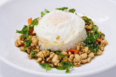 Chicken sauteed with garlic and hot basil set on steamed rice with fried egg photo