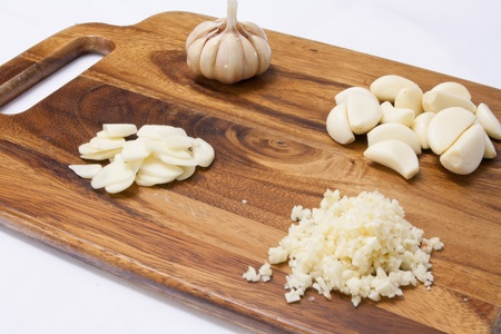 garlic on a wood cutting board over white background