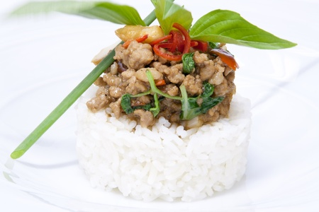 spicy chicken fried with hot basil on rice garnish with basil leaves photo