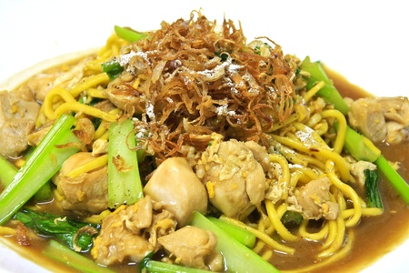 Egg noodle stir fried with chicken and bok-choy on top with crispy shallot Stock Photo