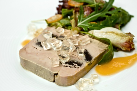 Sliced foie gras with sauce and vegetable leaf photo