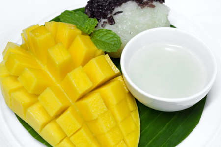 Black and white sticky rice with mango decorate with mint photo