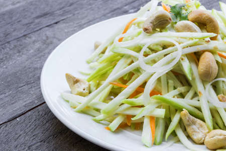 Green mango salad with carrot and cashew nuts photo