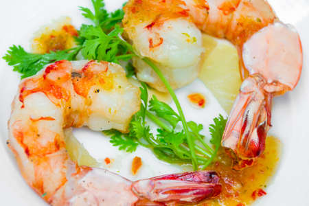 Grilled tiger prawn decorate with coriander leaf and lemon