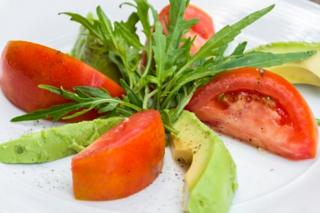 Arugula avocado and tomato salad with olive oil photo