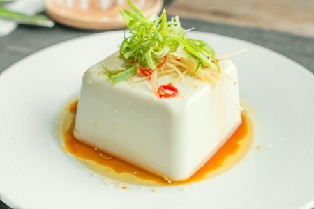 Silken tofu with gochujang and sesame oil decorate with spring onion and ginger