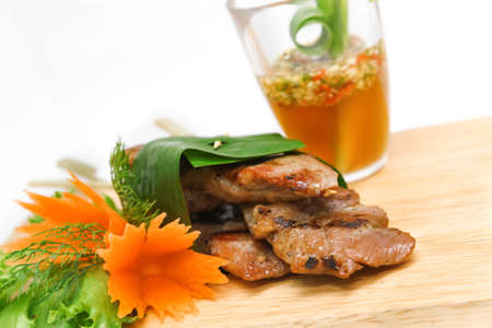 Roast pork wrapped in banana leaves and served with seafood sauce