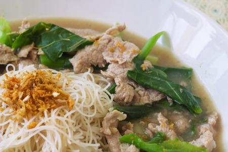 vermicelli  noodles topped with pork and kale photo