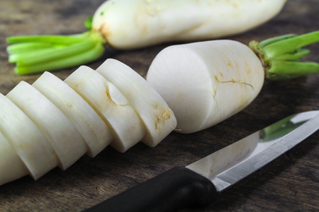 fresh slices white radish on wooden background, healthy vegatable