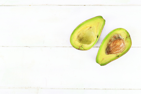 halved  half: Ripe avocado with leaves on a white background