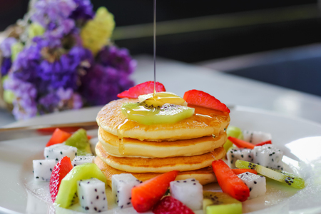 Pancakes for breakfast topped with strawberry and kiwi