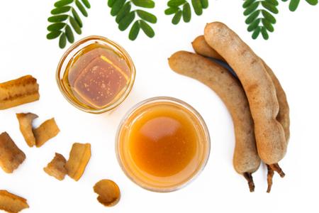 Tamarind and tamarind juice with honey on white background