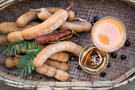 Tamarind and tamarind juice with honey on wooden background