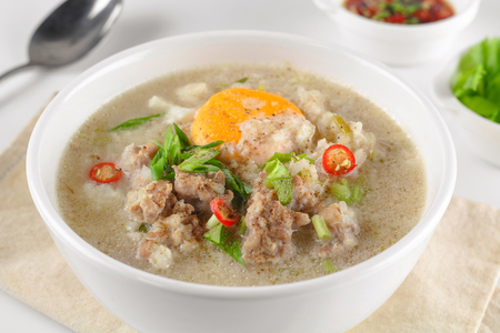 Congee with minced pork and boiled egg in bowl