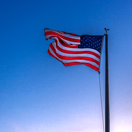 American flag flying in the breeze with blue sky background Editorial