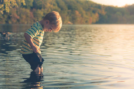 wading: Boy Wading into Lake Stock Photo