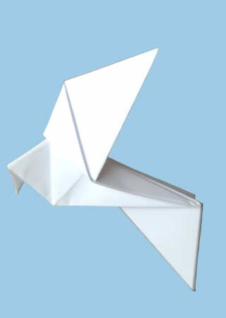 white origami paper bird on a blue background, referring to concepts such as freedom, lightness, the art of flying, as well as environmental concerns photo