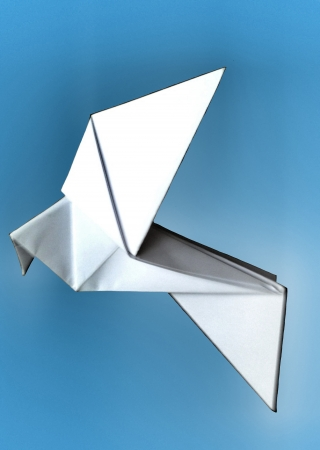 paper folding: representation of a glowing white origami paper dove on a blue background, referring to concepts such as freedom, lightness, the art of flying, as well as environmental concerns Stock Photo