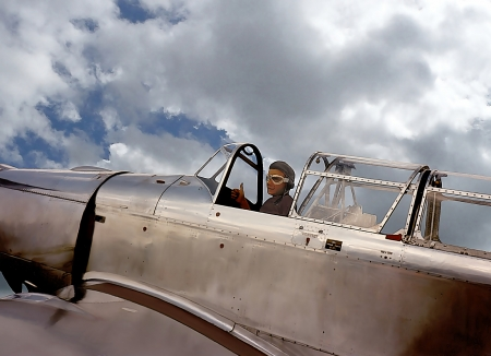 weaponry: Illustration of a pilot in the cockpit of a warbird, smiling and giving the thumb up, referring to concepts such as retro military aircrafts, aviation in general, as well as history and adventure Stock Photo