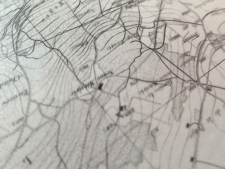 geographic: closeup view of a geographic map detail, showing a land area with a network of roads and isolated buildings, as well as level curves, with a selective focus on the upper side of the picture