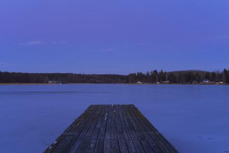 Blue winter evening and Woodbridge in frosen lake