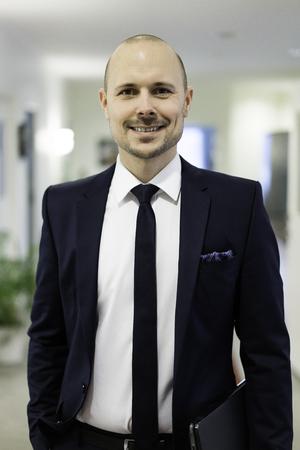 Swedish caucasian businessman. European Scandinavian. Smiling standing. Costume, suit, tie and laptop. Stock Photo