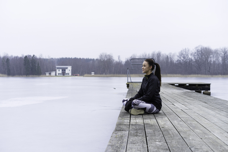 Beautiful Swedish caucasian fitness girl sitting on Woodbridge outdoor by the lake in winter landscape.