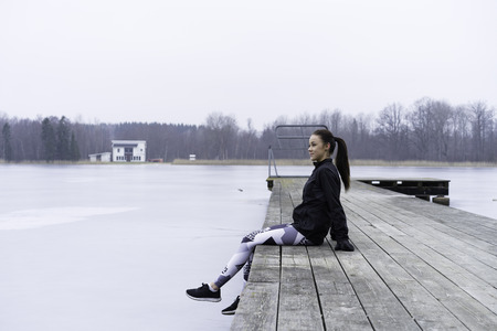 Swedish caucasian fitness girl sitting on Woodbridge outdoor by the lake in winter landscape.