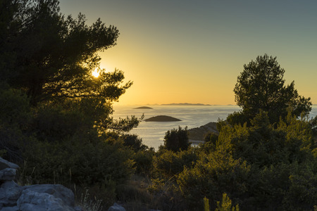 Beautiful nature and landscape photo of Croatia and Adriatic Sea. Nice, warm summer evening with clear yellow sky and lovely ocean. Calm, joyful and happy image.