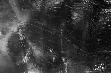 Beautiful background image of ice at winter. Nice details and structures. Abstract black and white photo with cracks, lines and pattern. Calm and peaceful picture.