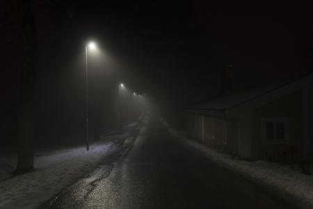 Foggy night in Sweden Scandinavia Europe. Beautiful, mystical and abstract photo of dark winter evening with mist in air. Calm, peaceful outdoors image with lights, lamps and road. Stock Photo
