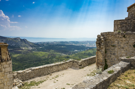 Fortress of Klis outside city of Split in Dalmatia Croatia. Beautiful old ruins and Buildings on high mountain top over the Adriatic Sea. Nice architecture of stone constructions. Ancient Royal Castle