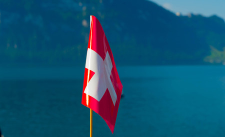 Flag of Switzerland against the backdrop of the mountains near Lake Lucerne.