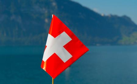 Flag of Switzerland against the backdrop of Lake Lucerne. Stock Photo