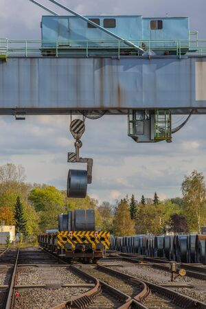 Andernach, Rhineland Palatinate, Germany - October 25, 2019: a big crane bridge has lifted a metal coil to load it onto a waggon Editorial