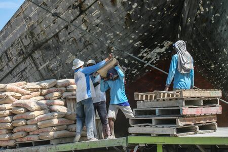 Jakarta, Indonesia - July 13, 2009: unskilled workers loading sacks from a truck onto a wooden transport vessel Editorial